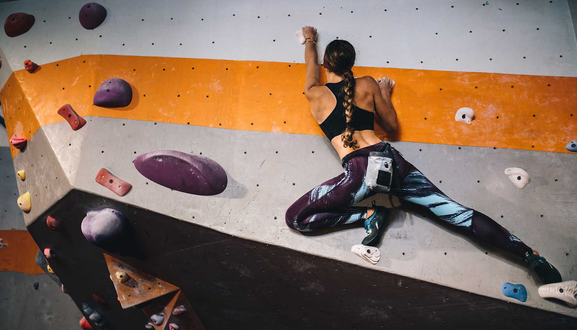 Woman learning the art of rock climbing at an indoor climbing center.
