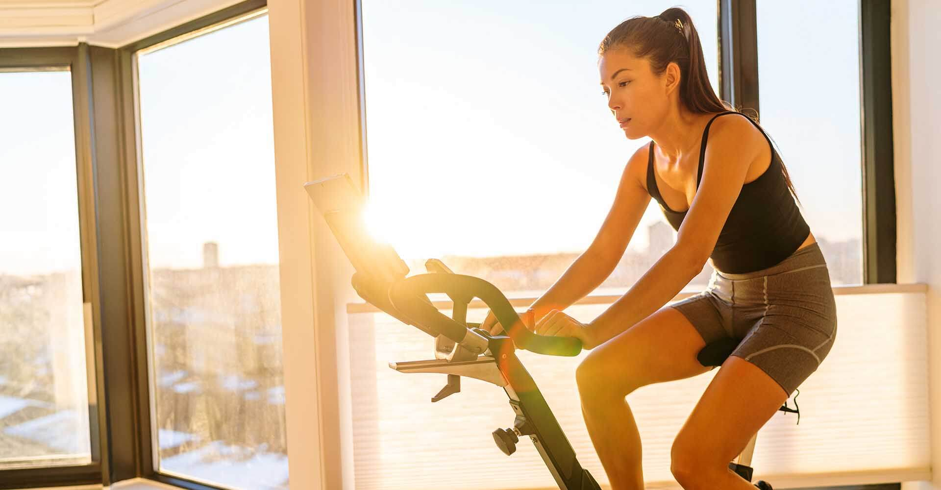 Home fitness workout woman training on smart stationary bike indoors.