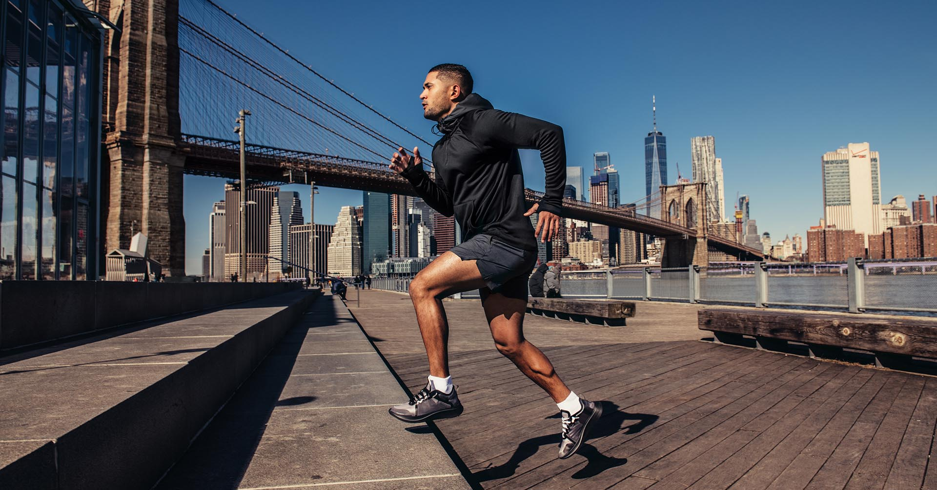 Athelte man running in New York City street wearing sport clothes.