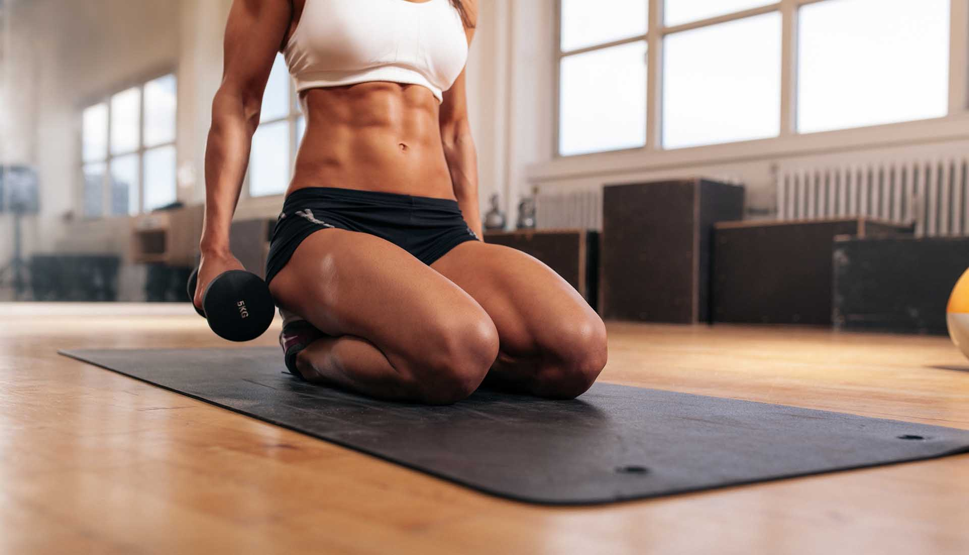 Cropped image of muscular woman exercising with dumbbells while sitting on fitness mat in gym.