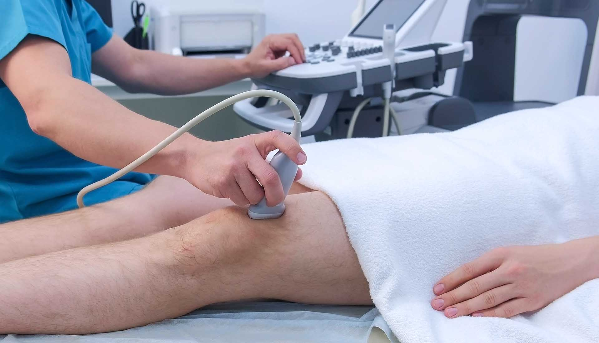 Doctor makes ultrasound of knee joint.