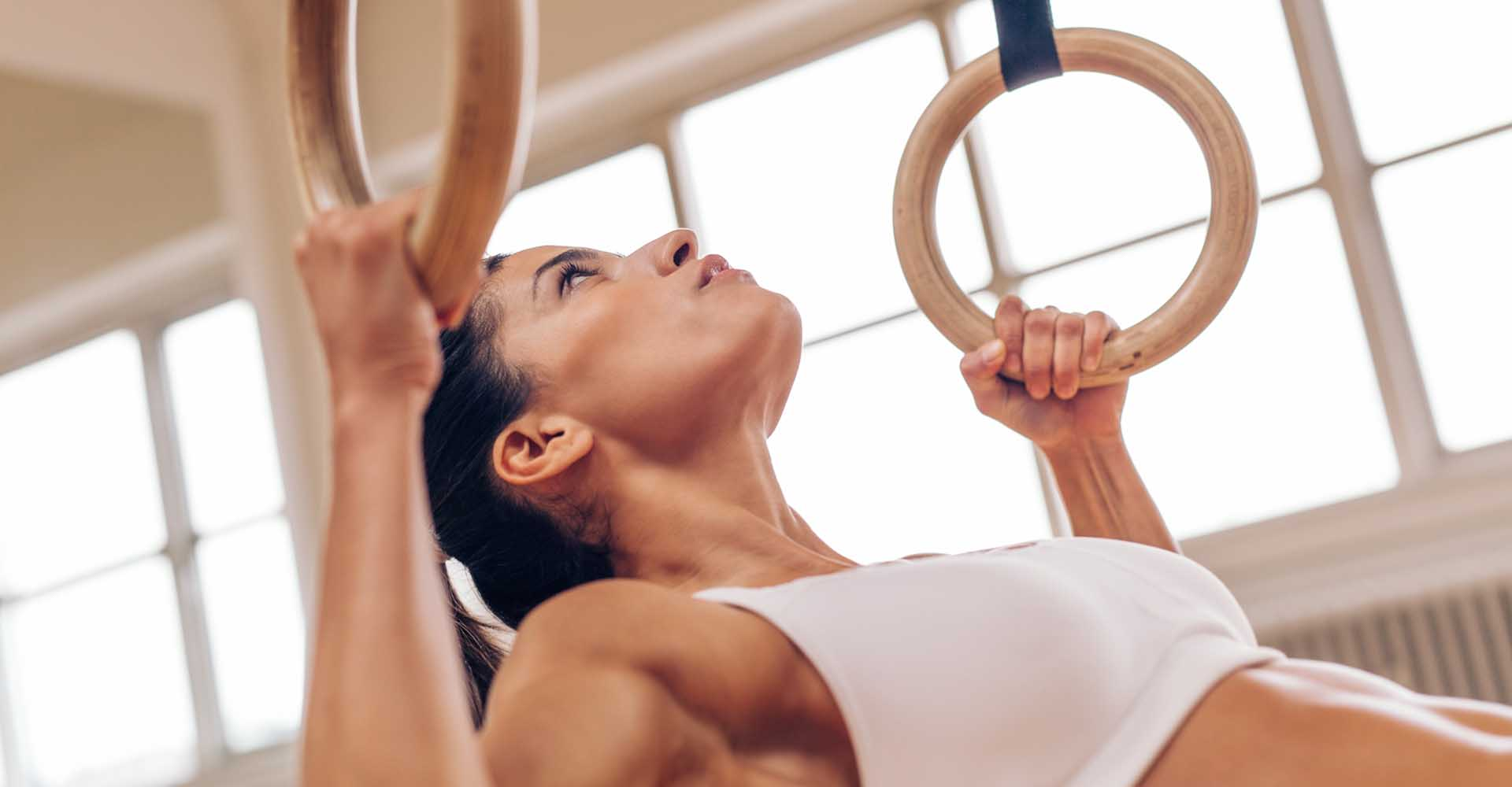 Strong young woman doing pull-ups with gymnastic rings.