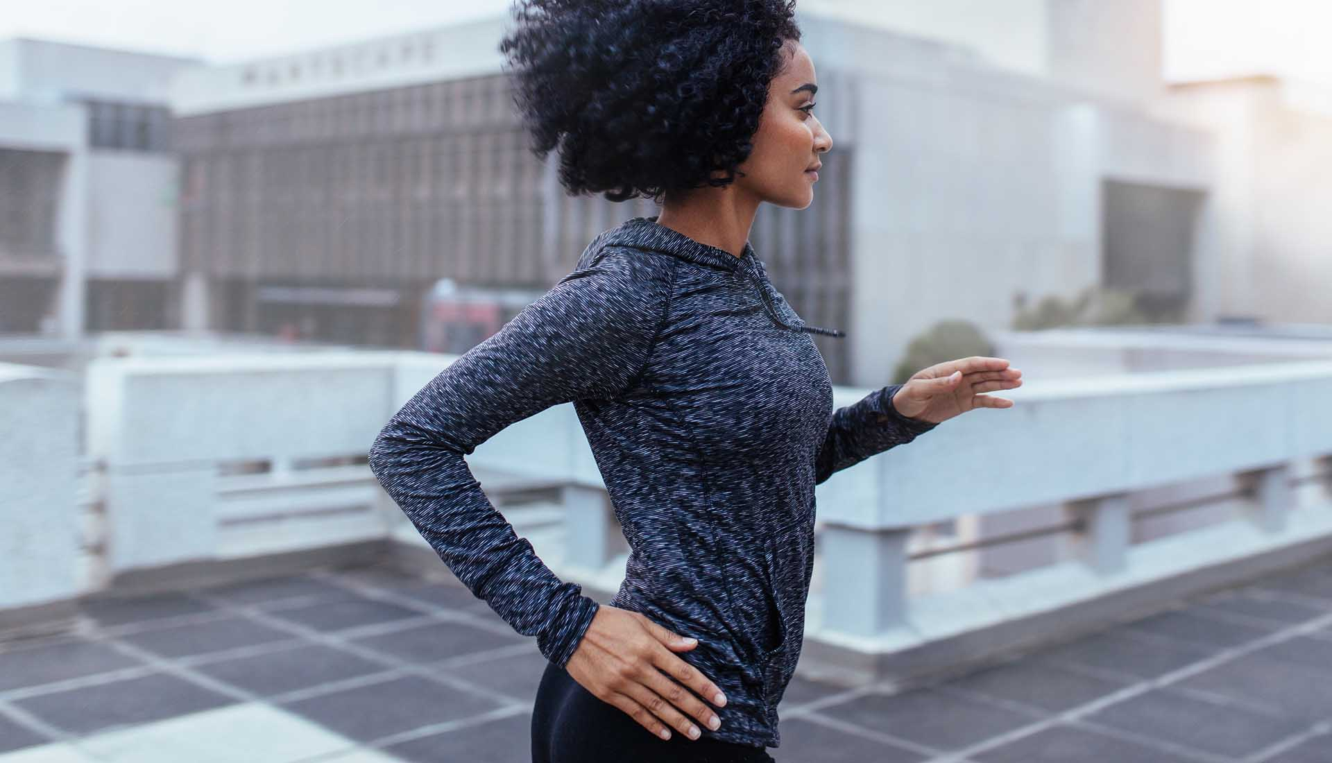 Female athlete in jogging in city.